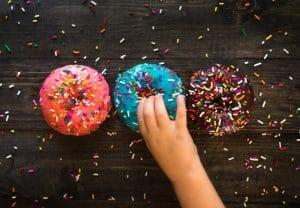 Zuckerkonsum bei Kindern hat Spätfolgen - Kind nimmt Donut